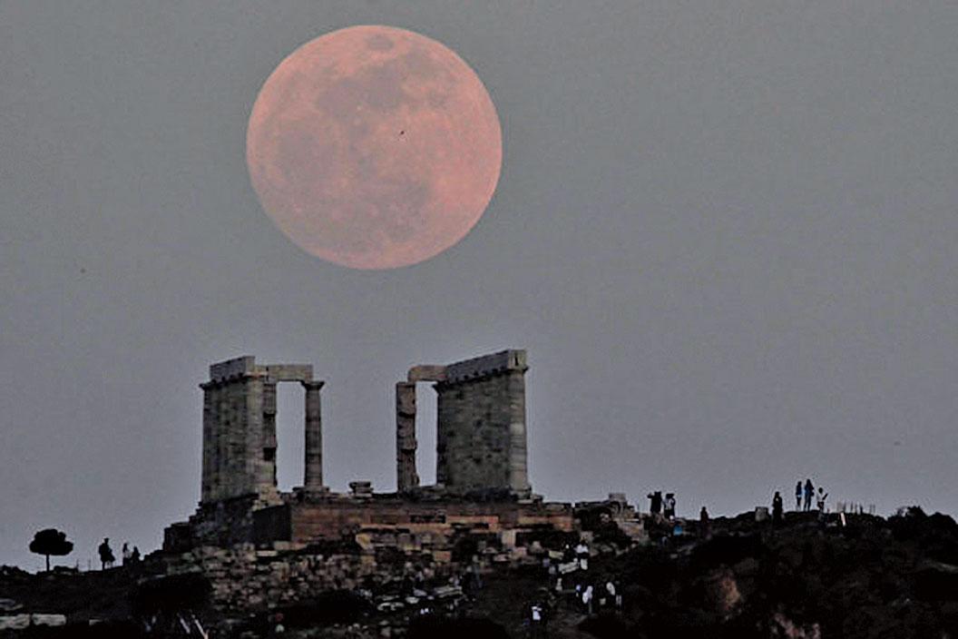 超級月亮照耀下的希臘雅典的一座古老廟宇。(ARIS MESSINIS / AFP)