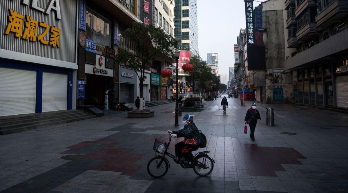 正遭受中共病毒(俗稱武漢病毒、新冠病毒)疫情的中國武漢市空蕩蕩的大街上偶有戴著口罩的市民路過。(Stringer/Getty Images)