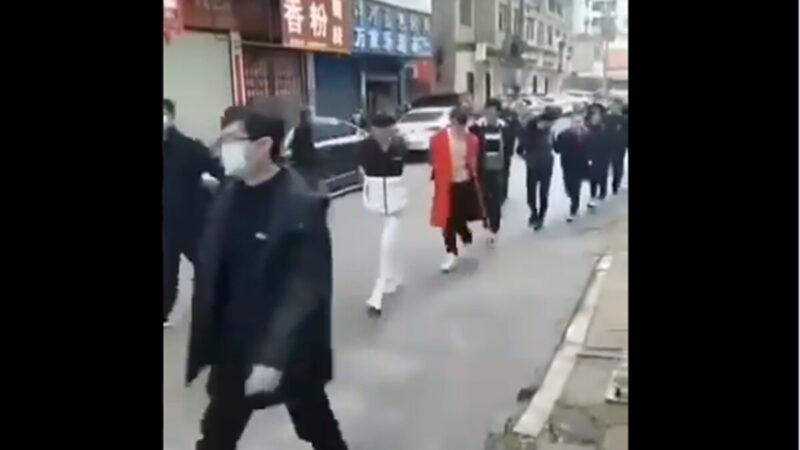 某地抓捕大批不戴口罩的人,並把他們捆綁起來,集體遊街示眾。(影片截圖)