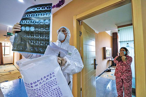 2月3日,武漢一家醫院的醫生在檢查肺部CT的圖片。(AFP)
