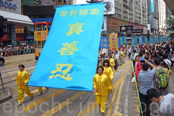 2014年7月19日,逾九百名法輪功學員在香港港島區舉行7.20十五周年反迫害集會遊行,呼籲各界制止中共迫害法輪功。隊伍從北角英皇道出發,途經多個鬧市區抵達政府總部,吸引眾多中港民眾和遊客駐足觀看。(潘在殊/大紀元)