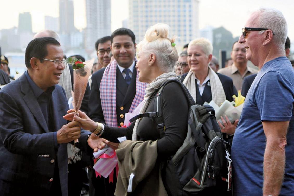2020年2月13日威士特丹號郵輪在施亞努港停靠後,14日柬埔寨總理洪森(中)親自與每位旅客握手並且獻花表示歡迎,現場無人配戴口罩。(AFP)