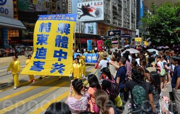 適逢法輪功7.20反迫害15年活動,來自各國的逾9百名法輪功學員在香港北角英皇道遊行到政府總部,呼籲全球制止中共迫害和停止活摘器官,吸引許多民眾觀看。(宋祥龍/大紀元)