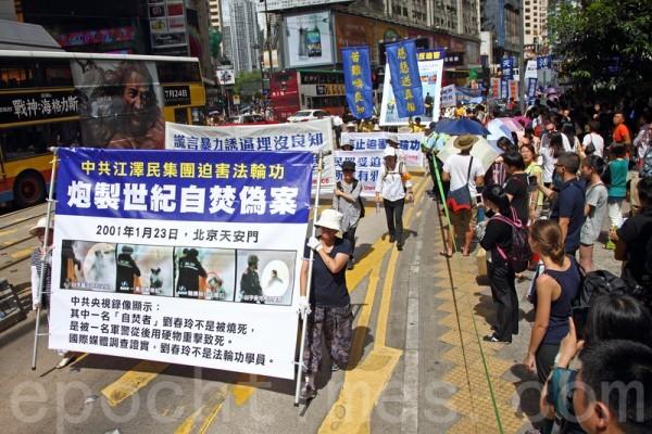 2014年7月19日,逾九百名法輪功學員在香港港島區舉行7.20十五周年反迫害集會遊行,呼籲各界制止中共迫害法輪功。隊伍從北角英皇道出發,途徑多個鬧市區抵達政府總部,吸引眾多中港民眾和遊客駐足觀看。(潘在殊/大紀元)