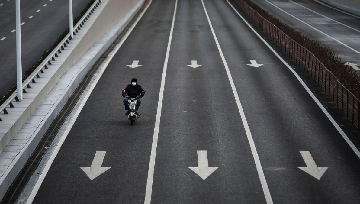 中國湖北省武漢市2020年2月16日下令實施24小時封閉式管制後,一個市民騎電單車出現在空蕩盪的街道上。(Getty Images)