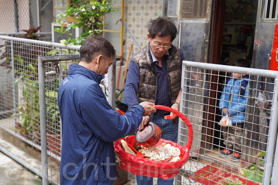 村民提著象徵「天姬船」的竹籃到家家戶戶拜訪收集衣紙寶燭等物品。(陳仲明/大紀元)