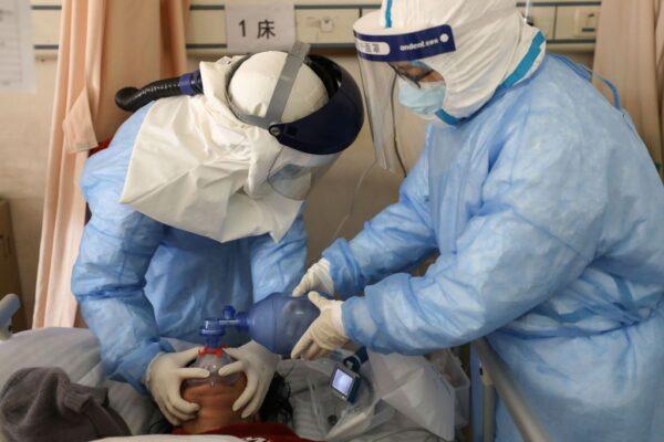 圖為武漢紅十字醫院醫生治療新冠肺炎病人。(STR/AFP via Getty Images)