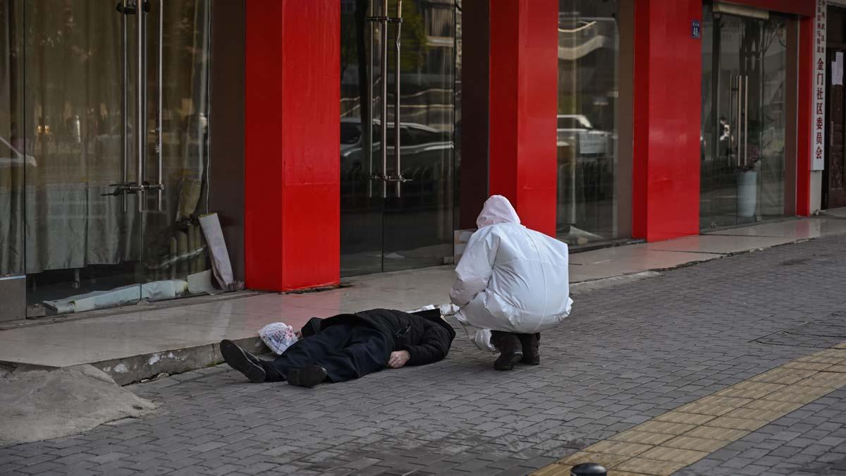 法新社1月30日拍攝的照片,一名白髮老人倒斃在武漢街邊。(HECTOR RETAMAL/AFP via Getty Images)