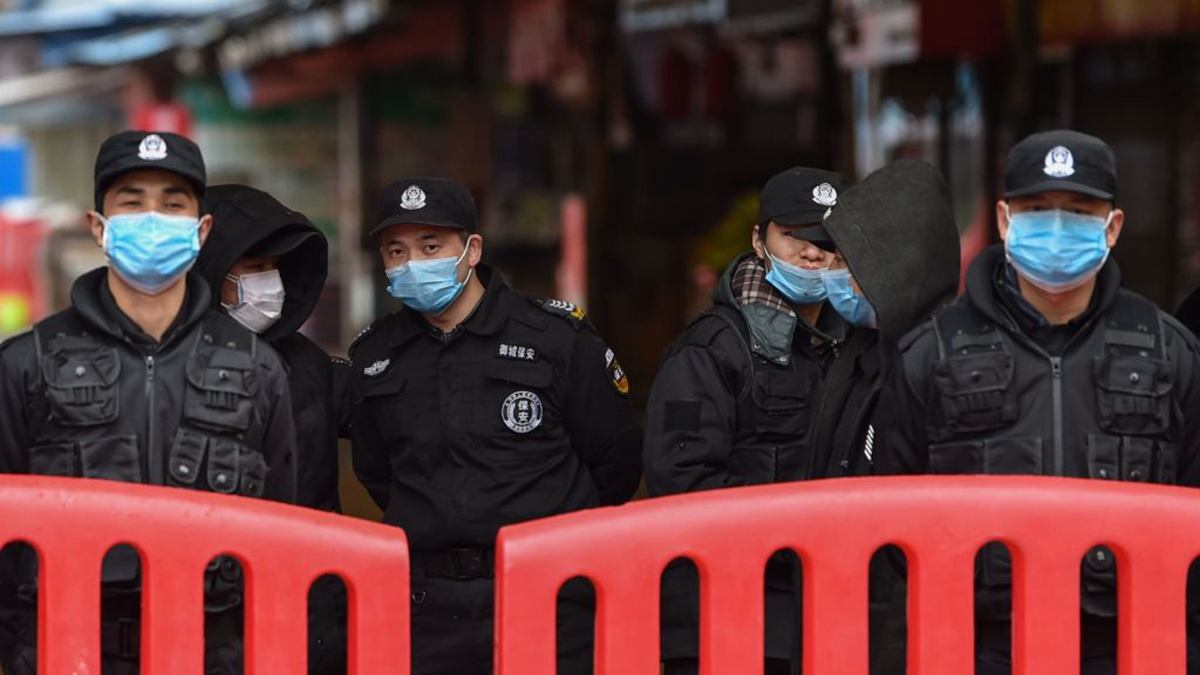 中共當局防疫從封城升級到封床。圖為武漢一群安保人員在封鎖路口。(HECTOR RETAMAL/AFP via Getty Images)