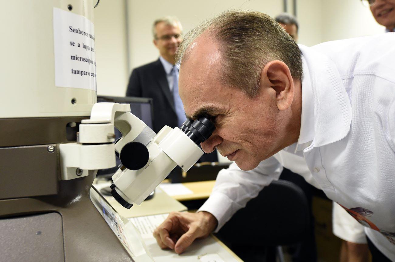 科學家在巴西發現一種被稱為Yaravirus的神秘病毒。圖為2016年2月19日,巴西衛生部長卡斯特羅(Marcelo Castro)藉由顯微鏡觀看寨卡病毒(Zika virus)的樣本,與本文無關。(EVARISTO SA/AFP via Getty Images)