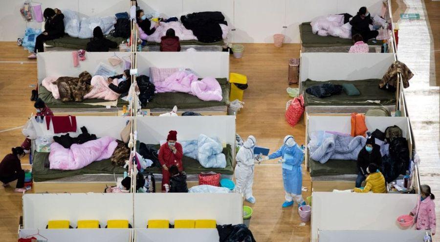 圖為中國湖北省武漢市體育館內設立的臨時醫院2020年2月18日夜間醫務人員在巡查症狀比較輕微的中共病毒患者。(STR/AFP via Getty Images)