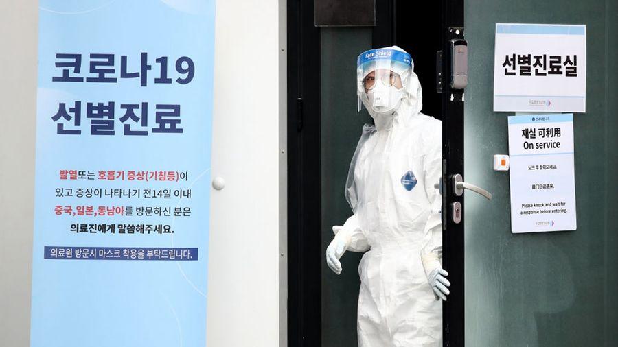 南韓疫情大爆發,三軍淪陷,總統府警衛隔離。圖為首爾醫療中心一名醫護人員打開門。(Chung Sung-Jun/Getty Images)