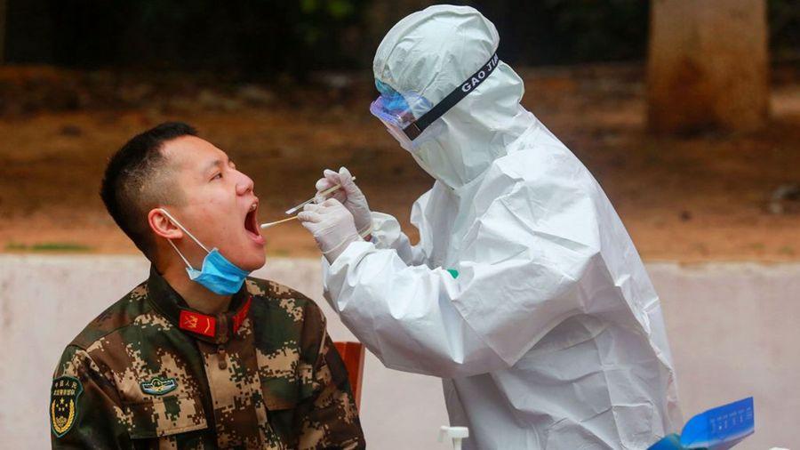 一名醫護人員正從一名軍人口中採集樣本。(STR/AFP via Getty Images)