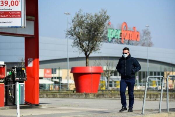 2020年2月22日,一名戴著口罩的男子走過米蘭東南部科多諾空無一人的街道。(MIGUEL MEDINA/AFP via Getty Images)