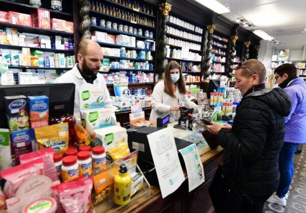 2020年2月22日,位於米蘭東南部的科多諾一家藥局,一名戴著口罩的藥劑師向客戶介紹防疫產品。(MIGUEL MEDINA/AFP via Getty Images)