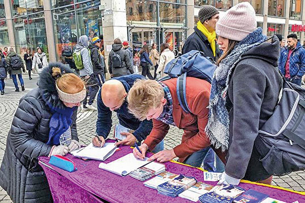 2020年2月15日,在斯德哥爾摩市區音樂廳旁,人們簽名支持法輪功學員反迫害。(明慧網)