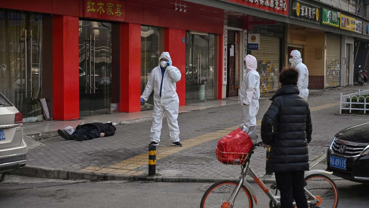 2020年1月30日,武漢公安和醫護一起,處理倒斃街頭的屍體。(HECTOR RETAMAL/AFP via Getty Images)