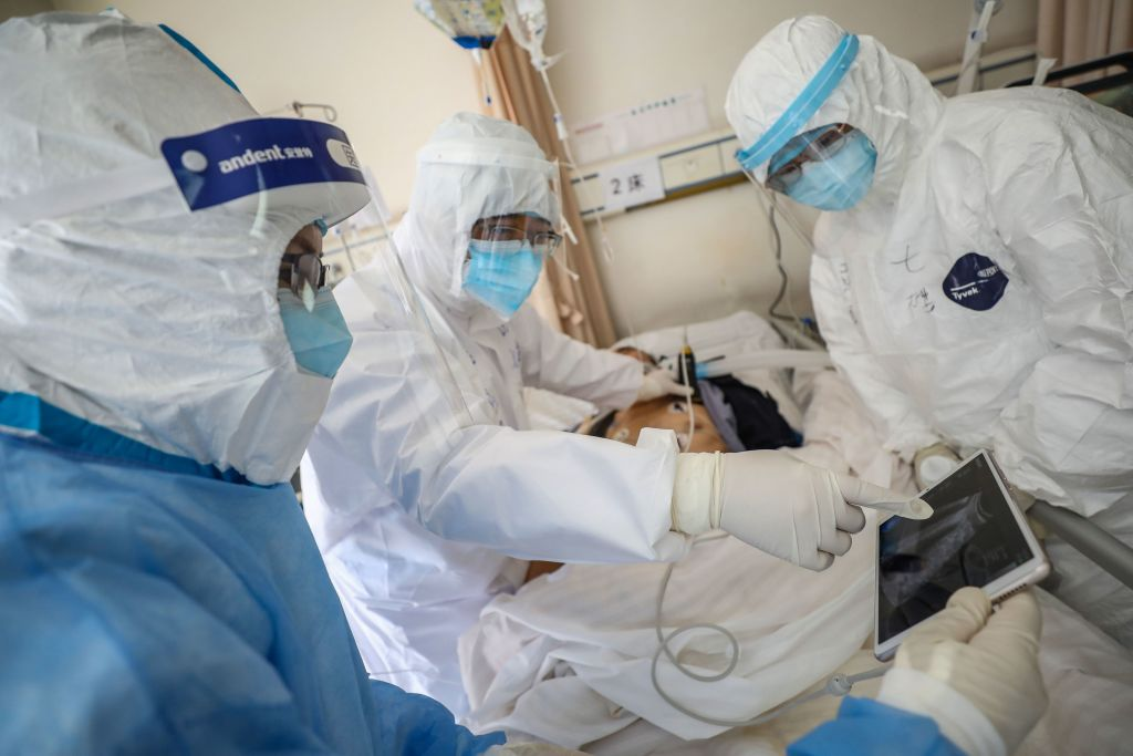 這張攝於2020年2月16日的照片顯示,一名醫生在湖北省武漢市武漢市紅十字會醫院檢查一名感染了中共病毒(俗稱新冠病毒、武漢病毒)的患者時正在查看圖像。(STR/AFP via Getty Images)