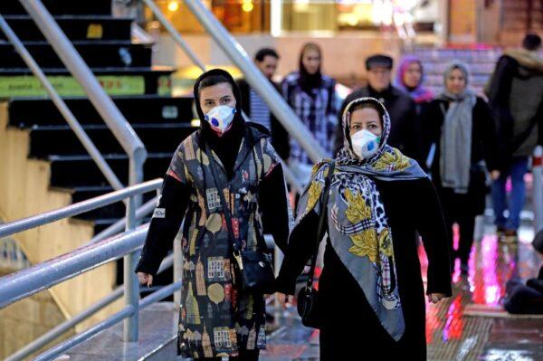 圖為,2020年2月20日,婦女在戴口罩走在伊朗首都德黑蘭的一條街道。(ATTA KENARE/AFP via Getty Images)