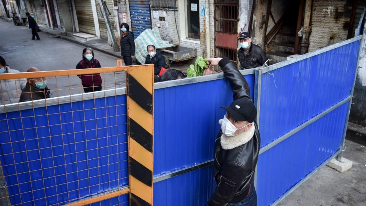 武漢市一個被封閉的街道,一名男子從隔離牆外把蔬菜送進去。(STR/AFP via Getty Images)