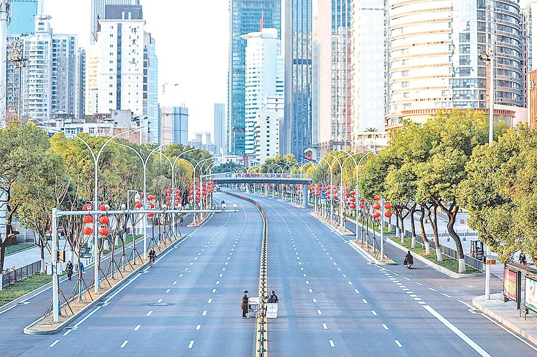 2020年2月20日,兩名工作人員運送蔬菜到武漢市的一家醫院,越過一條空空盪盪的大馬路。(STR / AFP)