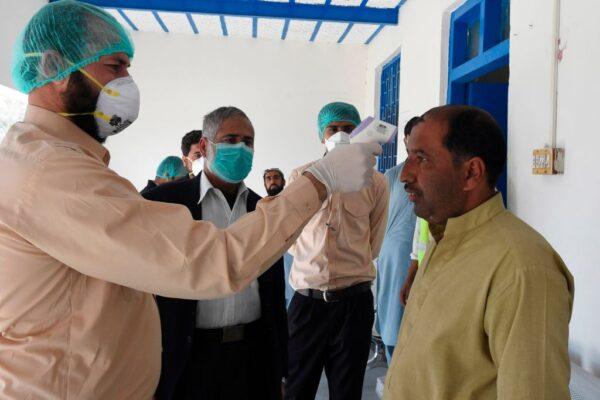 2020年2月25日,巴基斯坦-伊朗邊境小鎮塔夫坦(Taftan),一名醫生量測從伊朗隔離區返回的一名男子體溫。(BANARAS KHAN/AFP via Getty Images)