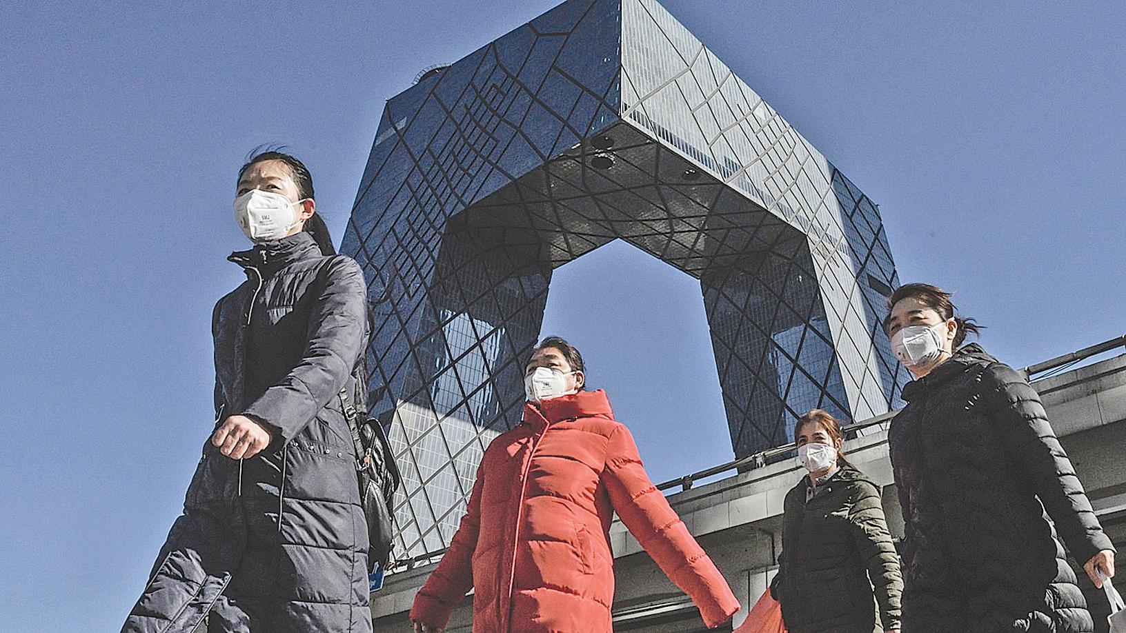2月17日載著口罩的路人經過北京央視大樓。 (Getty Images)