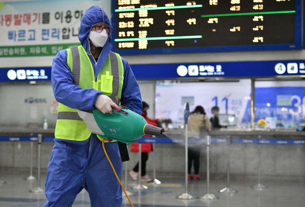 2020年2月26日,一名穿著防護裝備的工作人員在大邱火車站噴灑消毒劑。(JUNG YEON-JE/AFP via Getty Images)