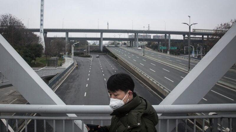 圖為一名男子站在武漢馬路天橋上。(Getty Images)