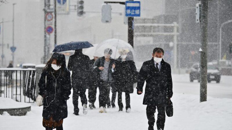 圖為,2020年2月3日,日本札幌降雪期間,民眾在街上行走時戴著口罩。(CHARLY TRIBALLEAU/AFP via Getty Images)