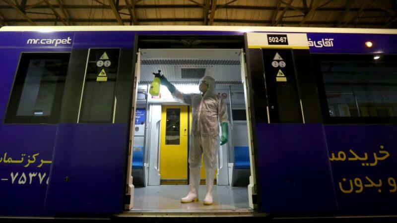 2020年2月26日,一名穿著防護裝備的工作人員在德黑蘭消毒地鐵車箱。ATTA KENARE/AFP via Getty Images)