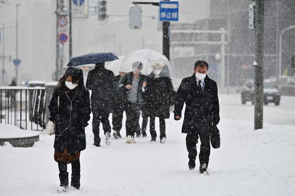 日本中共肺炎(俗稱武漢肺炎、新冠肺炎)疫情延燒,截至周四(2月27日)上午,已有896人確診,7人死亡。本月開始有16家分店,對上門購買口罩的消費者,強迫搭配營養飲品等商品。圖為,2020年2月3日,日本札幌降雪期間,民眾在街上行走時戴著口罩。(CHARLY TRIBALLEAU/AFP via Getty Images)