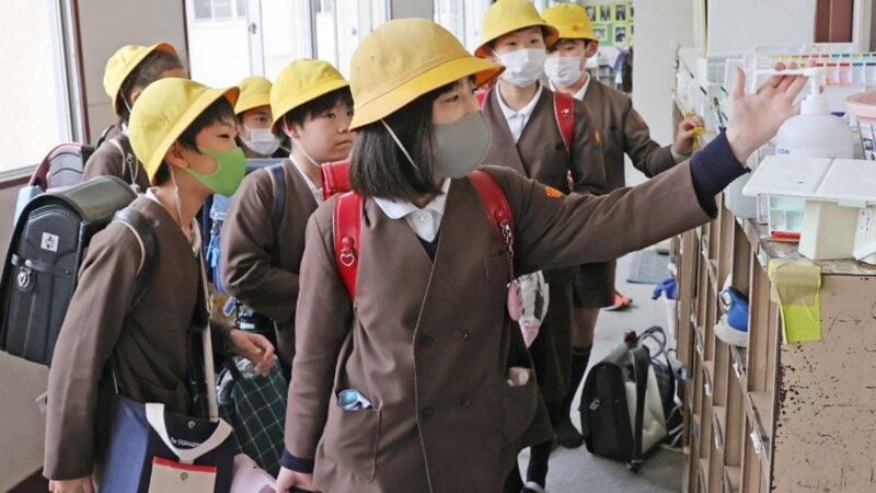 圖為戴著口罩的日本小學生,在離開學校前對雙手進行消毒。(STR/JIJI PRESS/AFP via Getty Images)