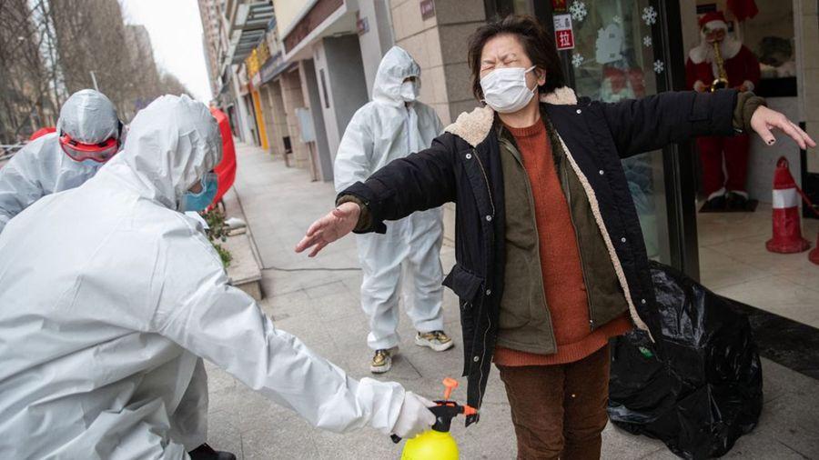 一名武漢婦女正在接受志願者的消毒。(STR/AFP via Getty Images)