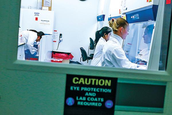 2 月28 日,美國新澤西州某實驗室研究人員對冠狀病毒所開發的藥物進行測試。(AFP)