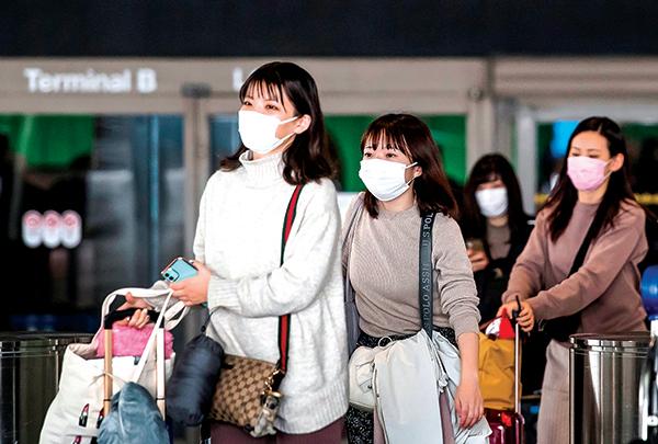 隨著新冠狀病毒蔓延,各國紛紛祭出更嚴格的旅行限制措施。圖為2月29日,戴著口罩的乘客抵達美國加州洛杉磯的機場。(Getty Images)