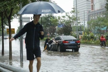 7月20日北京街頭,人們奮力推淪陷在水中的車。(Lintao Zhang/Getty Images)