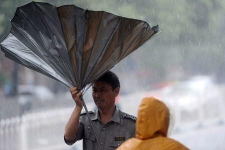 7月20日,北京男子走在街頭,傘被狂風吹翻。暴雨造成至少1死34傷。(STR/AFP/Getty Images)