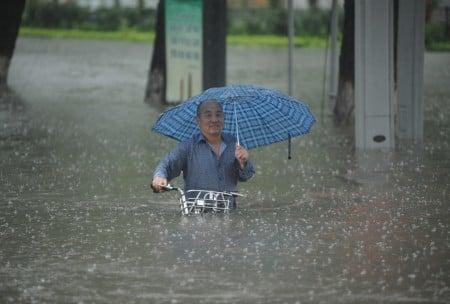 7月19日,山西太原的居民在洪水中推車而行。(VCG/Getty Images)