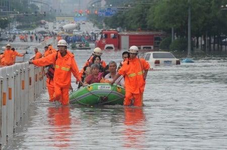 7月20日,太原街頭,救援人員幫助受難的居民。(VCG/Getty Images)
