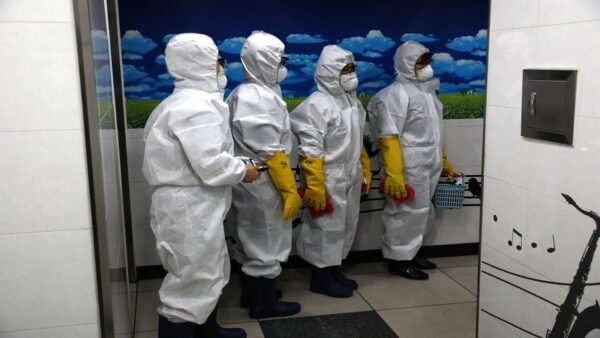 圖為2月28日,穿著防護服的南韓工作人員準備消毒。( Chung Sung-Jun/Getty Images)