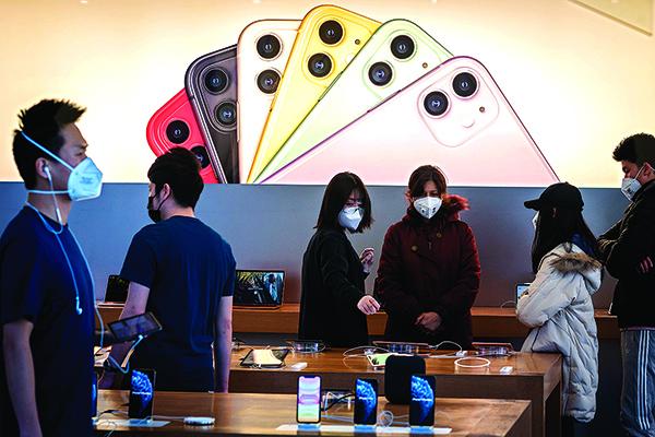 蘋果預估到3月底的財測可能無法達標,且全球iPhone供應可能受限。圖為2月22日,北京蘋果專賣店裏的員工和顧客均戴口罩。(AFP)