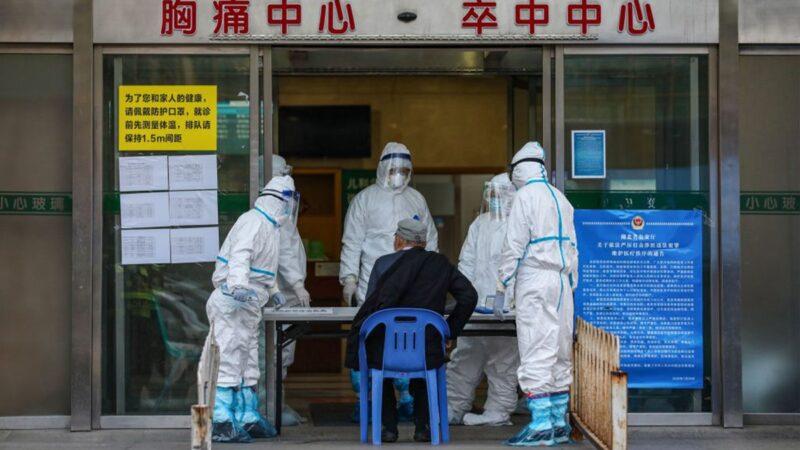 圖為武漢醫護人員在接診患者。(STR/AFP via Getty Images)