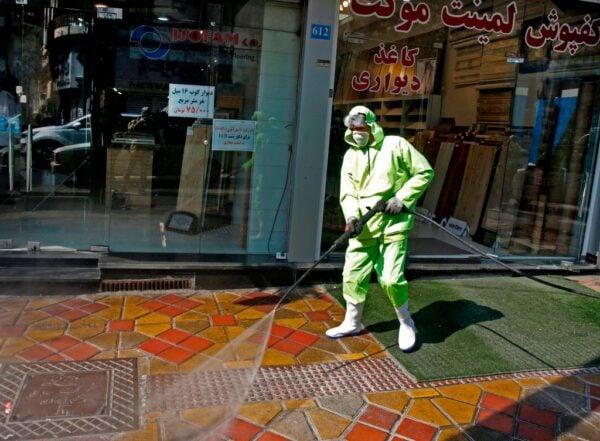 2020年3月5日,伊朗首都德黑蘭一名穿著防護服的消毒人員噴灑街道消毒。(STR/AFP via Getty Images)