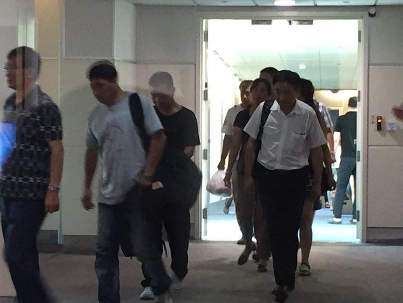 中國大陸在國道火燒車事件罹難的家屬,搭乘包機,21日已經抵達台灣,家屬神情哀傷。包機落地後,家屬分批搭乘16輛車前往中壢殯儀館。(中央社)