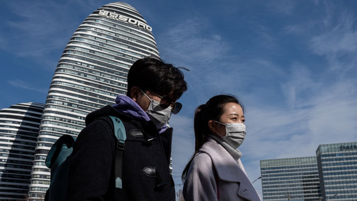 一對北京男女經過北京望京soho大樓前。(NICOLAS ASFOURI/AFP via Getty Images)
