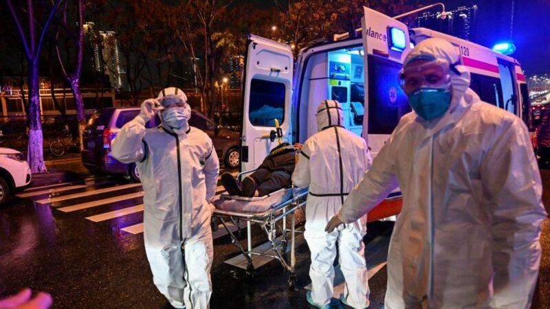 圖為1月25日,武漢醫務人員收治一位病人。(Photo by HECTOR RETAMAL/AFP via Getty Images)