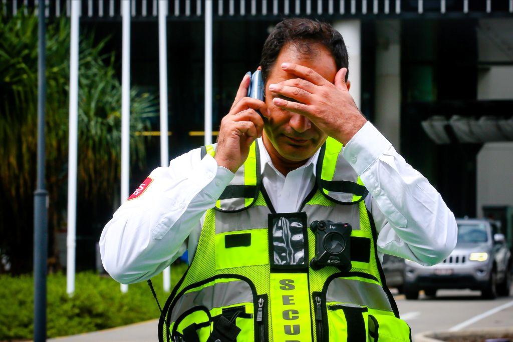2020年3月13日,一名警衛在巡邏黃金海岸大學醫院外的區域時與人通電話。(PATRICK HAMILTON/AFP/AFP via Getty Images)