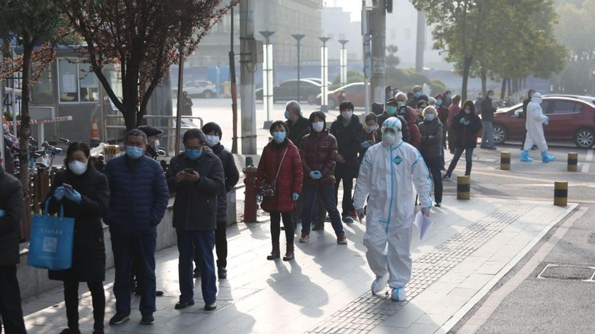 武漢市民戴著口罩排隊等候檢測。(STR/AFP via Getty Images)