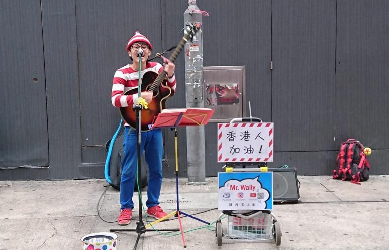旺角街頭,一日本青年獻唱,引來不少觀眾。(木子/大紀元)